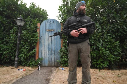 Matt Watts stands guard outside his home after many of his neighbors evacuated the area, in Estacada, Oregon, on Saturday. Many residents are concerned looters are breaking homes left empty by people fleeing the fires.