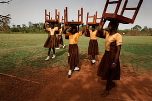 Schoolgirls in Ghana help prepare for the opening of the Maranatha Maternity Clinic by carrying chairs to the ceremony.