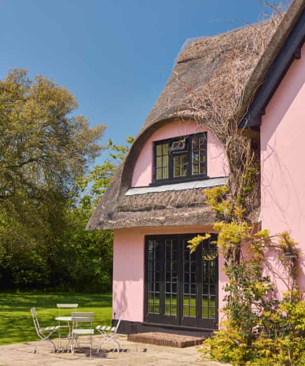 The pink walls and thatched roof of the home of fashion designers Justin Thornton and Thea Bregazzi in Walberswick, Suffolk