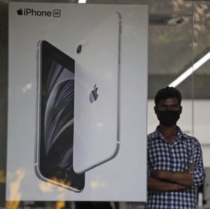 An employee stands by an image of an iPhone displayed at an Apple store in Ahmedabad, India, Saturday, 1 August, 2020.