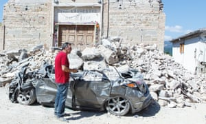 A man stands near his destroyed car, by a church that collapsed in Pescara del Tronto.