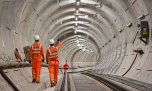 Engineers walk alongside completed tracks ready for the Crossrail service, one of London's hugely expensive rail infrastructure upgrades.