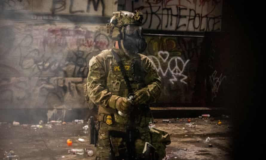 A federal officer holds a tear gas canister as protesters and officers clash in Portland, Oregon early on Saturday morning.