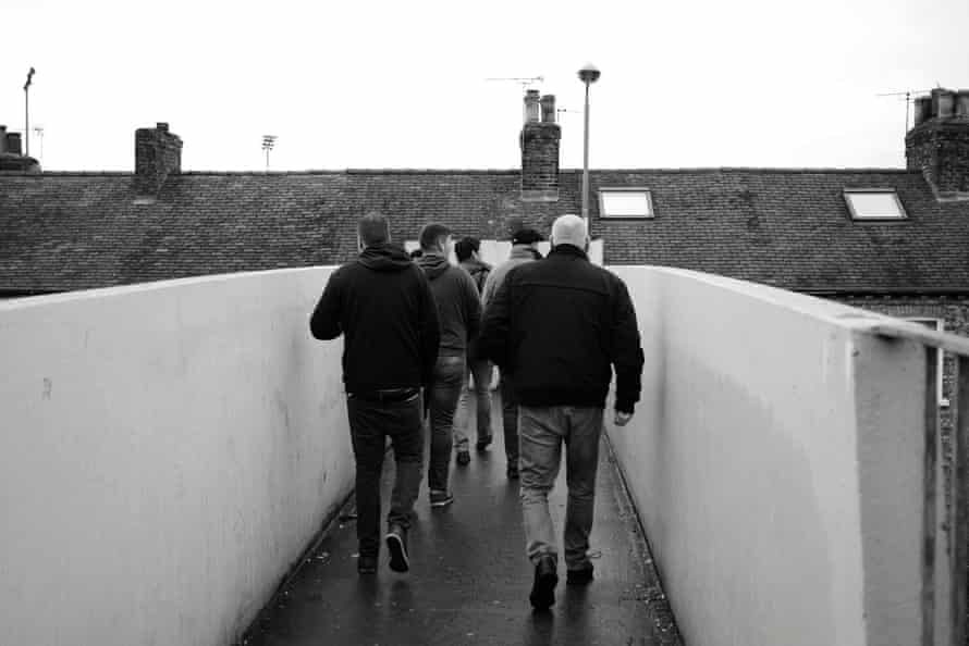 Fans cross the railway bridge on their way to the ground