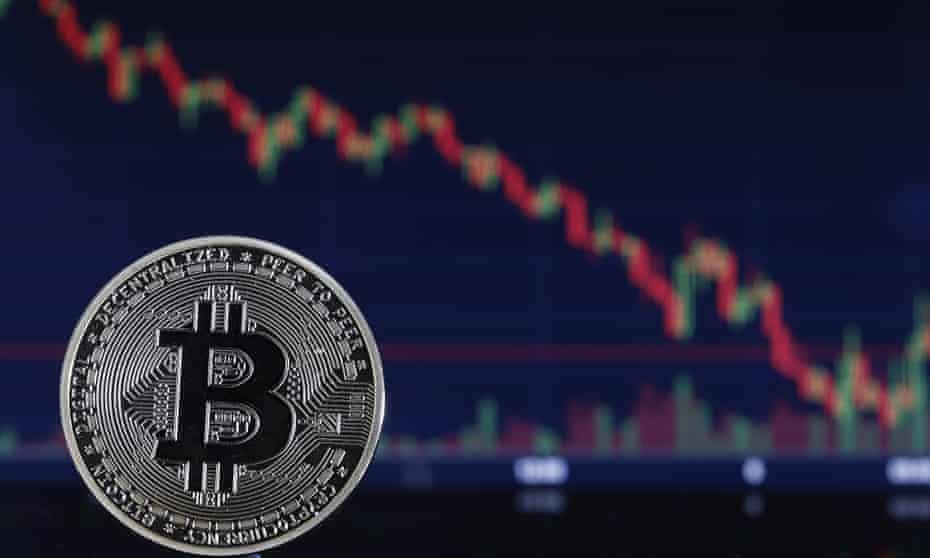 a bitcoin 'coin' and a graph showing a long steady fall