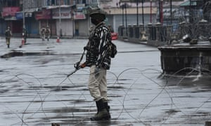 An Indian paramilitary soldier stands guard in Srinagar, Kashmir on Sunday.