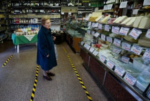 A woman waits to be served behind yellow lines that mark the distance customers have to keep between themselves in a grocery in the Trastevere area of Rome