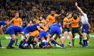 Michael Hooper (centre) of the Wallabies pushes over to score.