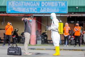 Medan, Indonesia: a refugee worker just arrived from Malaysia gets sprayed with disinfectant before entering a quarantine centre at Soewondo Airbase
