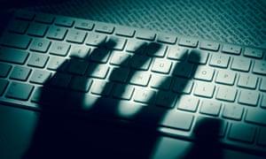 Shadowy hand over keyboard