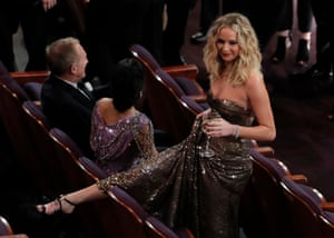 Actress Jennifer Lawrence pretends to climb over a seat