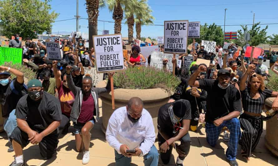 Protesters kneel in front of the Palmdale sheriff's station to demand an investigation into the death of Robert Fuller.