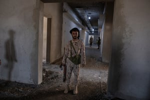 A soldier guards a delegation of foreign journalists at a hospital under construction in Ataq