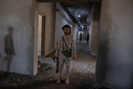 A soldier guarding a delegation of foreign journalists stands in a hospital that is under construction in Ataq.