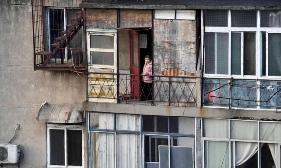 woman looks outside from the balcony at a residential compound in Wuhan, the centre of the novel coronavirus outbreak