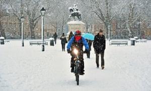 A cyclist rides through Queen's Square in Bristol