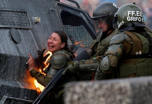 A riot police officer reacts having been engulfed in flames after a series of molotov cocktails were thrown in the direction of the police during protests in Santiago.