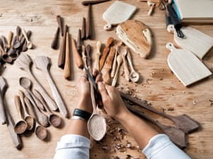The hands of wooden spoon carver Sophie Sellu, carving a spoon, with other spoons in the background
