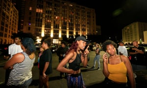 Dallas residents stand near the scene where four officers were shot and killed.