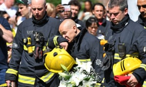 Firefighters look at floral tributes left in the aftermath of the Grenfell fire