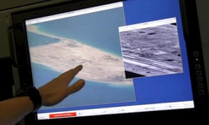 A US navy crewman aboard a P-8A Poseidon surveillance aircraft points to a computer screen purportedly showing Chinese construction on the reclaimed land of Fiery Cross reef in the disputed Spratly islands in the South China Sea.