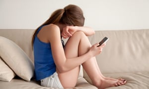 a teenage girl cries on the sofa reading a text message