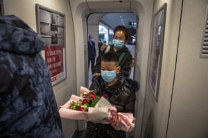 Passengers board the first train departing from a railway station after the lockdown is lifted in Wuhan