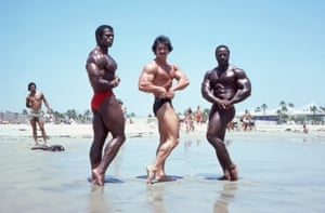 USA early 1970. Three male body builders on a beach