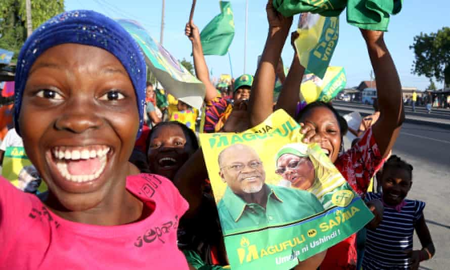 A Tanzanian supporter holds a poster featuring the newly elected president John Magufuli.
