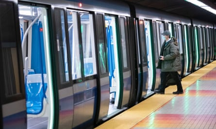 A commuter wearing protective mask boards a subway train in Montreal.