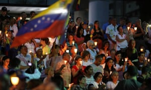 People attend a candlelight vigil held for victims of recent violence in Caracas on 5 May.