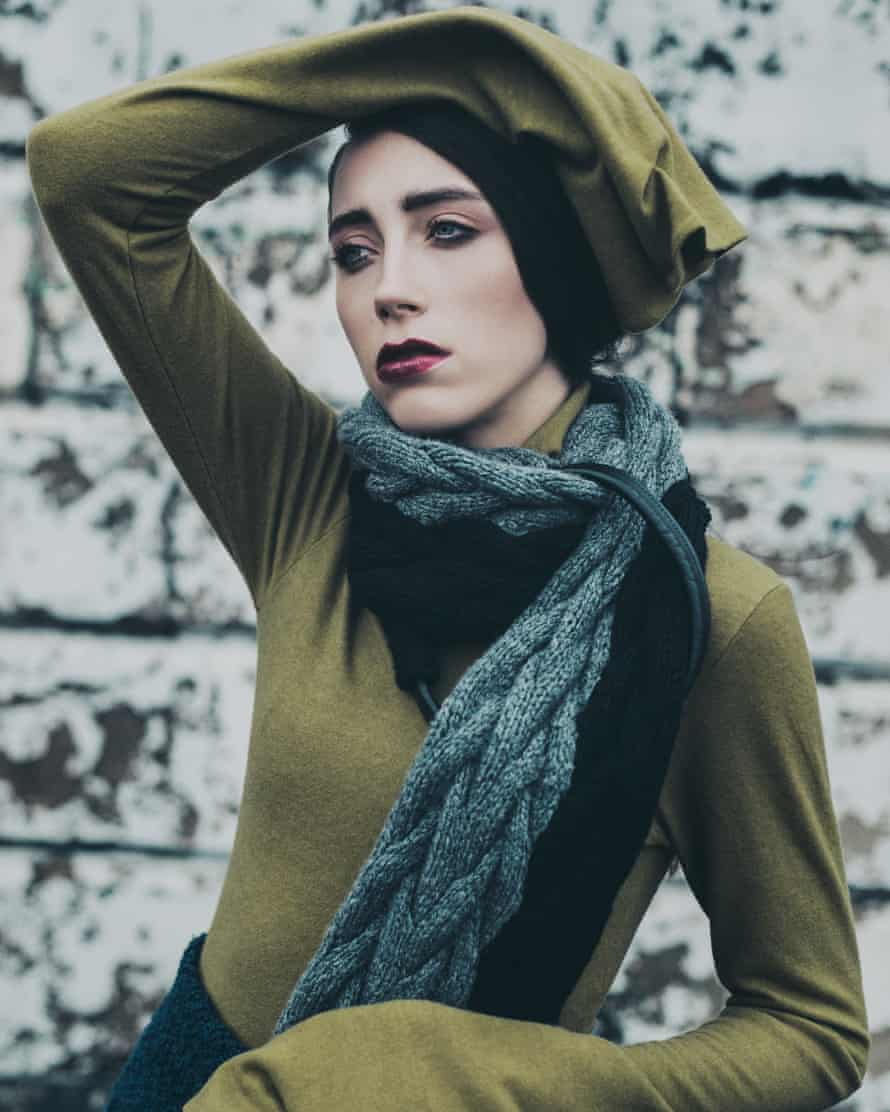 Marketing multifunctionality: what you may be wearing next winter, a green top with very long sleeves and a turquoise cardigan-like scarf.
