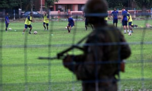 Real Kashmir Football Club players attend a training session as an armed security personnel keeps guard at Kalyani in Nadia district in the eastern state of West Bengal, India.