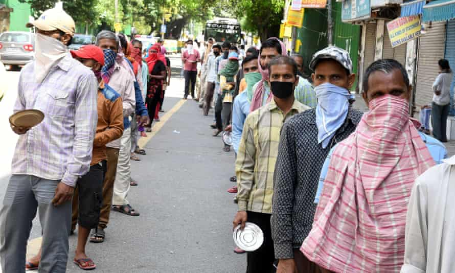 Indian labourers and daily wages workers queue for food in New Delhi, India, 7 April 2020.