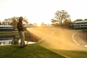 A member of the grounds crew waters the 17th green on an empty course after the cancellation of the The PLAYERS Championship and three consecutive events due to the COVID-19 pandemic as seen at The Stadium Course at TPC Sawgrass on March 13, 2020 in Ponte Vedra Beach, Florida.