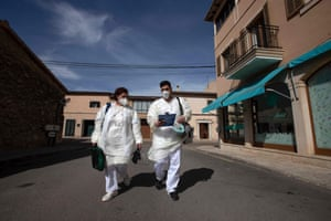 Nurses Sofia (left) and Borja walk down a street in Consell on the island of Mallorca during a vaccination campaign for people who are at high risk from coronavirus, 17 February 2021.