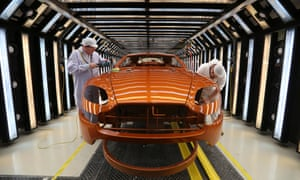 Employees polish the bodywork of an Aston Martin V8 Vantage  at Aston Martin Lagonda's manufacturing and assembly plant in Warwickshire.