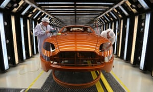 Employees polish the bodywork of an Aston Martin V8 Vantage at the manufacturing and assembly plant in Gaydon, UK