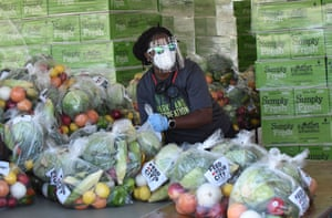 Miami, Florida, US, a volunteer helps sort out bags of produce and vegetables for The Feed Your City Challenge tour