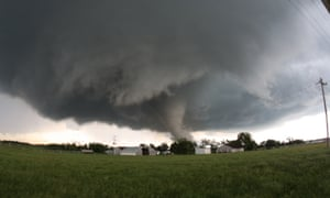 A tornado roars across farmland close to farm buildings in Katie, Oklahoma, USA
