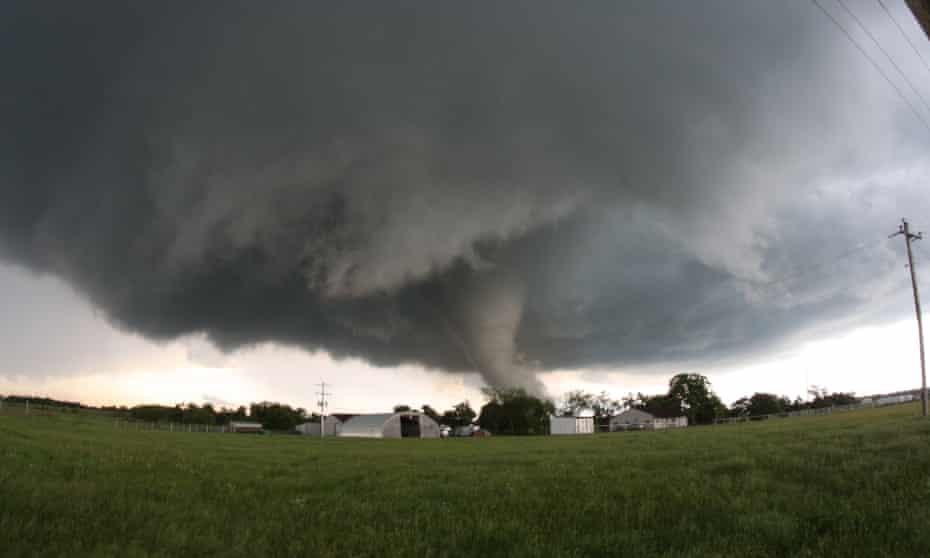 A tornado roars across farmland close to farm buildings in Katie, Oklahoma, USA