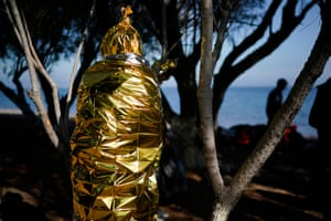 Skala Sikamineas, Greece A migrant keeps himself warm with a space blanket on a beach after making the crossing from Turkey to the Greek island of Lesbos. The influx of migrants continues forcing authorities to begin the relocation of refugees and migrants from the overcrowded Moria Camp to the mainland to ease pressure on the island camp