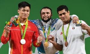 Kazakhstan's Nijat Rahimov, centre, poses with silver medallist Lyu Xiaojun, left, and bronze medallist Mohamed Mahmoud.