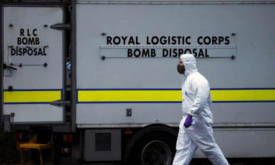 A police forensic officer walks past a bomb disposal unit van