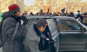 Activist Yang Chunlin is bundled into a car by authorities after protesting outside Wang Quanzhang's trial.