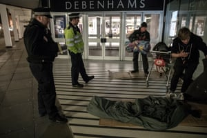Police officers moving on homeless men from a shopping centre