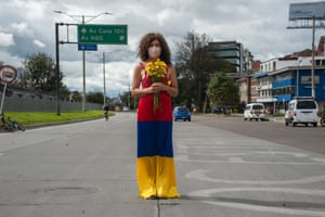 A woman stands in the middle of the road with a dress with the Colombian flag colours upside down as Colombia enters its third week of anti-government protests