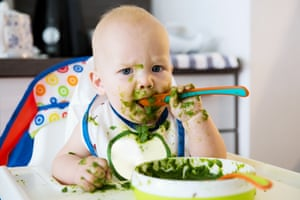 Adorable baby child eating with a spoon in high chair.