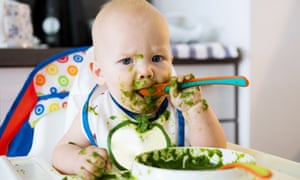 A baby at a high chair with a bowl of green puree and a good deal of it on the baby's face and hands