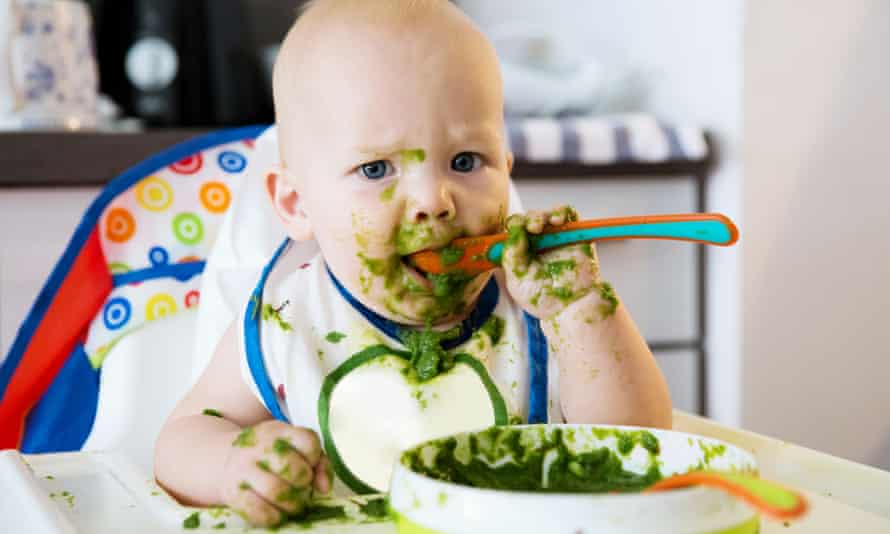 baby feeding - a very messy baby eating green mush in high chair.